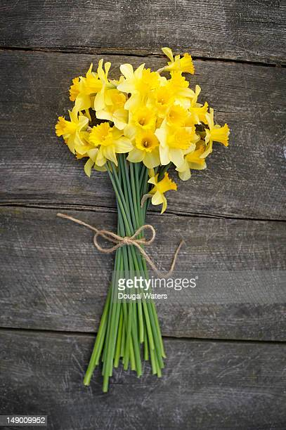 bunch of daffodils on a wooden table - daffodils stock photos and pictures