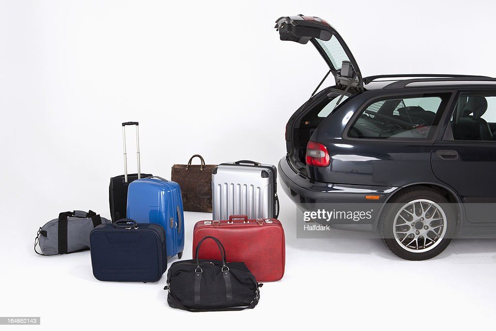 A bunch of different pieces of luggage next to an open car trunk : Stock Photo