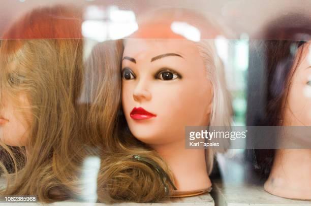 a bunch of female mannequin heads on a store shelf - poupée gonflable photos et images de collection