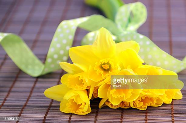bunch of flower with yellow daffodil and green ribbon