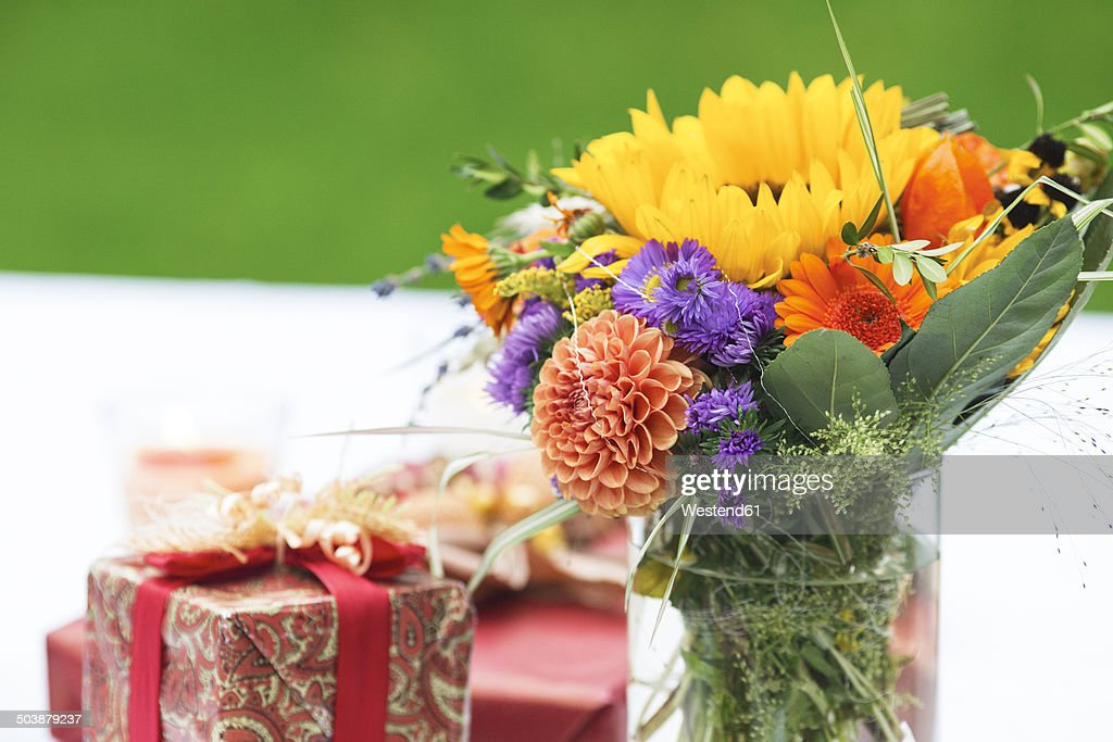 Bunch of flowers and gift on outdoor table getty images bunch of flowers and gift on outdoor table negle Gallery