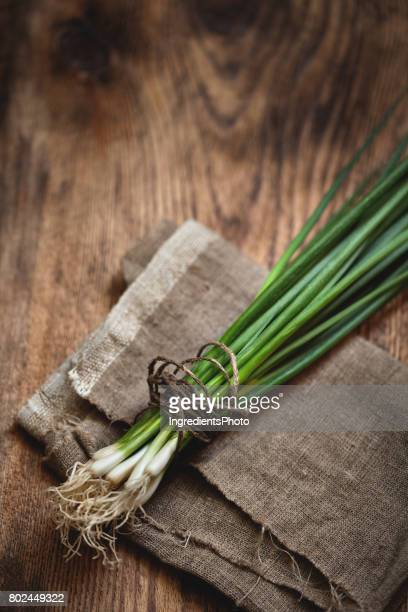 Bunch of fresh green onion on a wooden table.