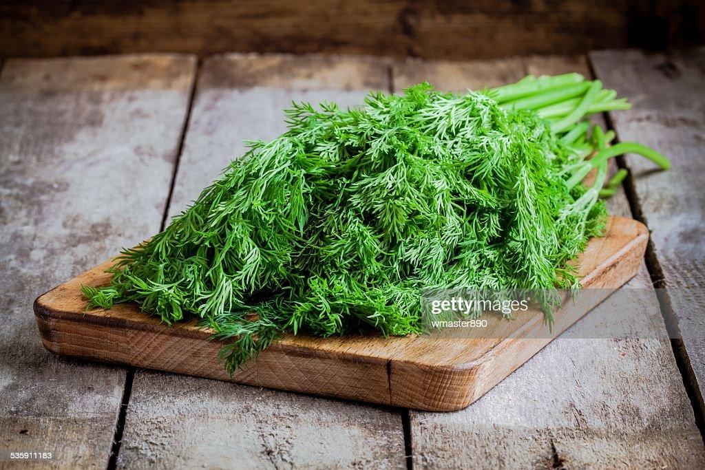 Racimo de eneldo orgánicos frescos en una tabla de cortar : Foto de stock