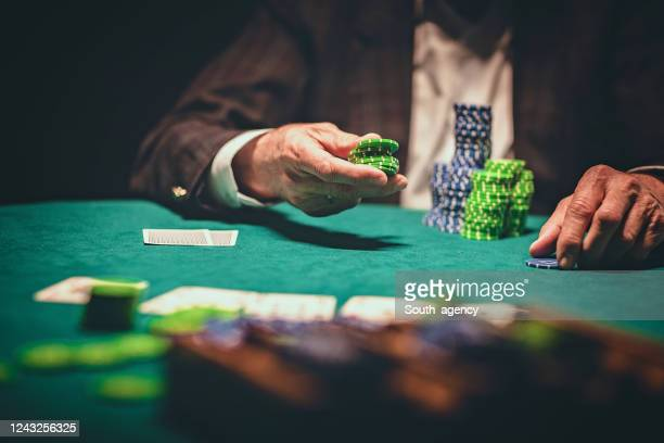 bunch of gambling chips in front of a man in casino - gambling table stock pictures, royalty-free photos & images