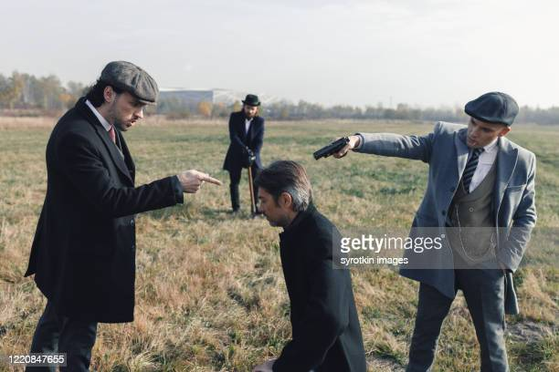 bunch of gangsters aiming at head of detective. - dead gangster stock pictures, royalty-free photos & images