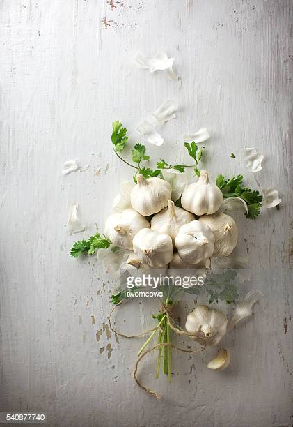 A bunch of garlic and fresh herbs tide up as a bouquet on white rustic background.
