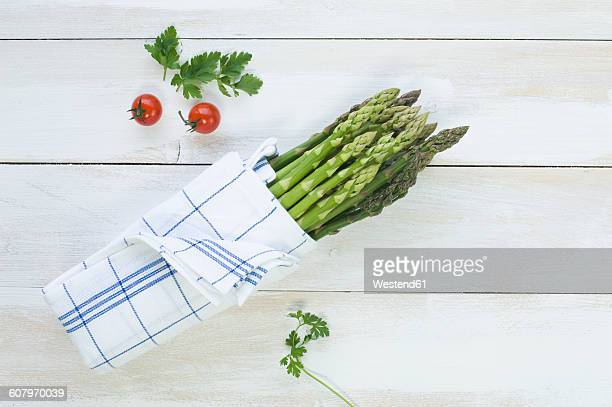 bunch of green asparagus wrapped in kitchen towel - flat leaf parsley stock pictures, royalty-free photos & images