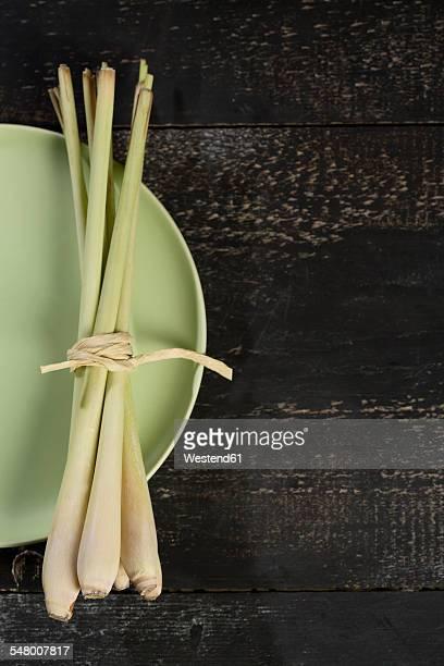 Bunch of lemongrass, Cymbopogon citratus, on plate and dark wood