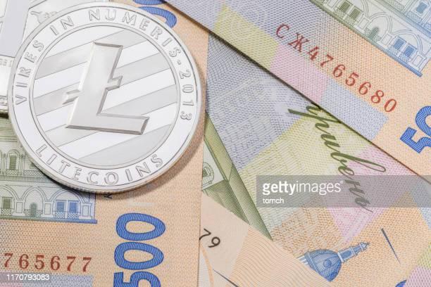 ein haufen litecoins auf 500 hryvnas hintergrund. - korruption stock-fotos und bilder