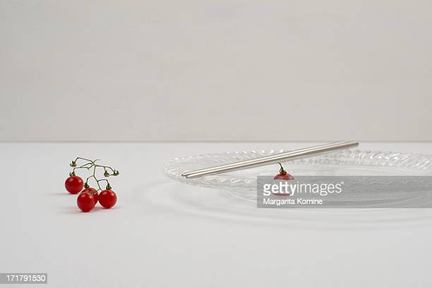 A bunch of micro tomatoes and chopsticks on plate