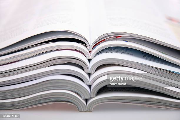 A bunch of open magazines stacked on top one another