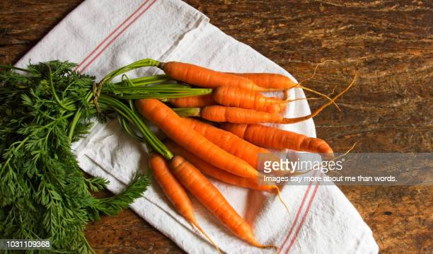 bunch of organic carrots on a dishcloth. still life - carrot stock pictures, royalty-free photos & images