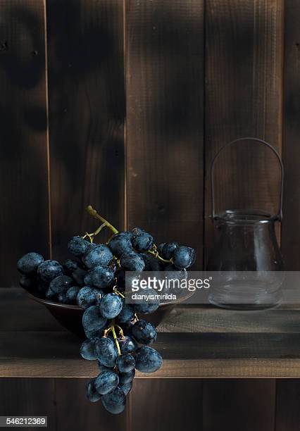 Bunch of red grape in bowl on table