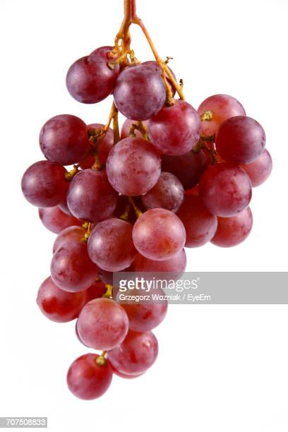 bunch of red grapes against white background - red grape stock photos and pictures