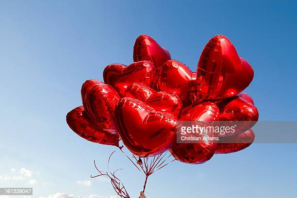 A bunch of red heart-shaped balloons