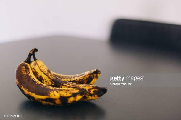 bunch of ripe, rotten bananas on a dark table - 熟した ストックフォトと画像