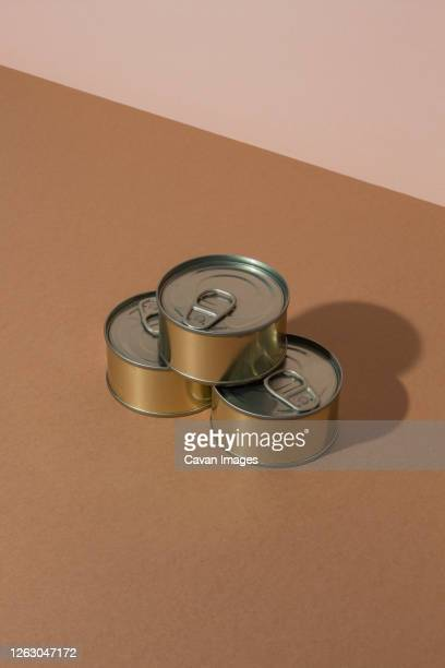 bunch of sealed tin cans with preserved food placed on brown surface - tin can stock pictures, royalty-free photos & images