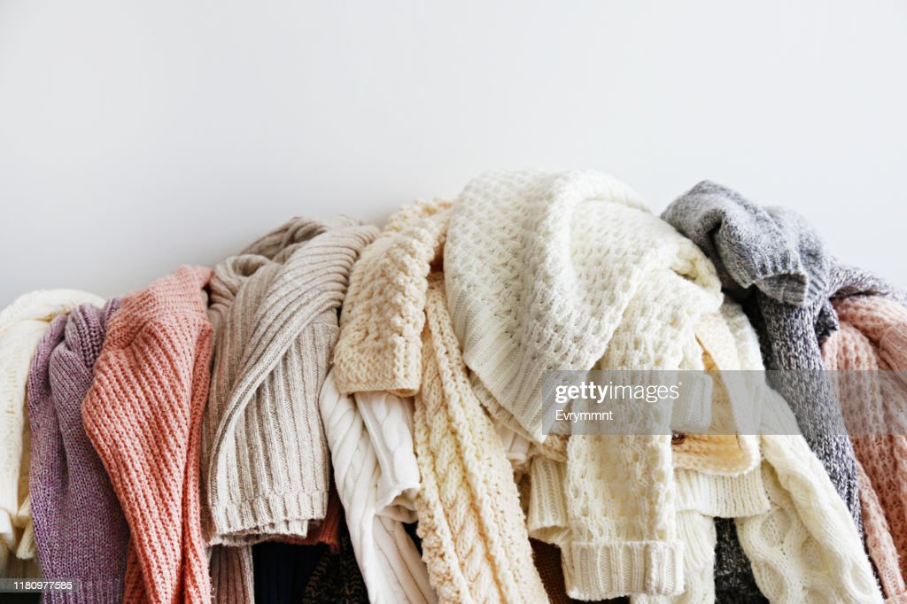 Bunch of sweaters of different material and knitting pattern in pile on gray sofa. : Stock Photo