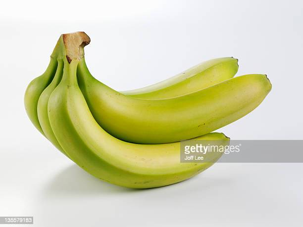 bunch of unripe bananas - unripe stock pictures, royalty-free photos & images