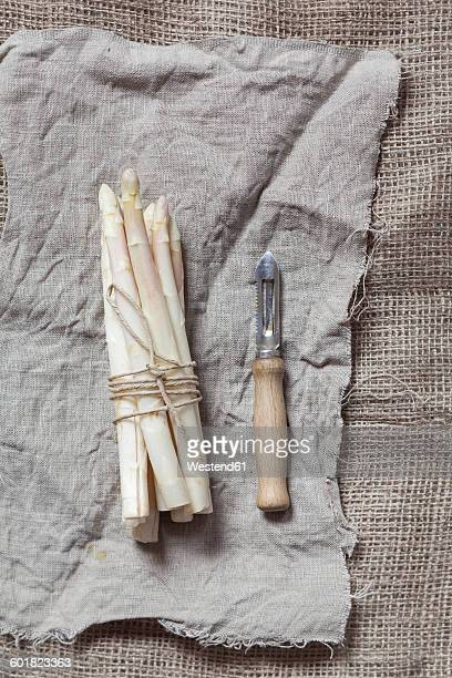 Bunch of white asparagus and peeler
