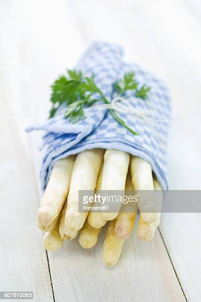 bunch of white asparagus wrapped in kitchen towel - peterselie stockfoto's en -beelden