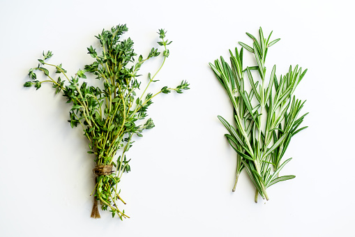 Bunches of tied thyme and rosemary on white background isolated 1030783200
