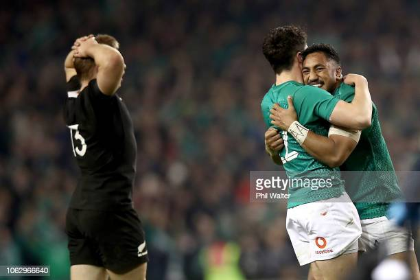 Bundee Aki and Joey Carbery of Ireland celebrate on full time as Jack Goodhue of the All Blacks looks dejected during the International Friendly...