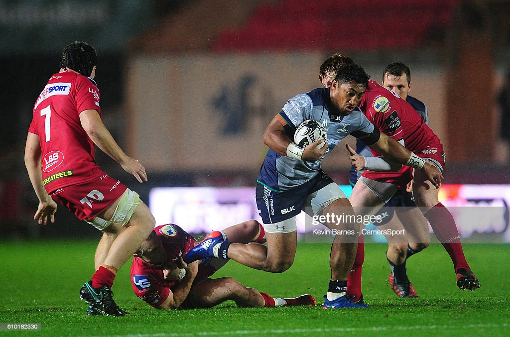 Bundee Aki of Connacht evades the tackle of Aled Davies of
