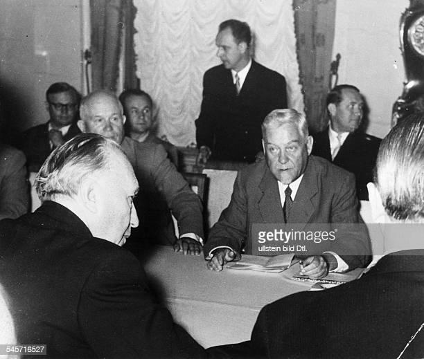 Bundeskanzler Konrad Adenauer am Konferenztisch imSpiridonowkaPalast ihm gegenüber linksNikita Chruschtschow rechtsMinisterpräsident Nikolai Bulganin