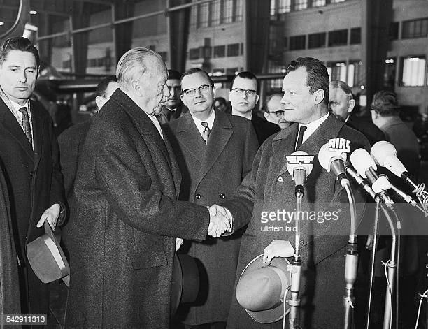 Bundeskanzler Konrad Adenauer und Willy Brandt der Regierende Bürgermeister von Berlin schütteln sich 1962 vor den Mikrophonen einiger Sendeanstalten...