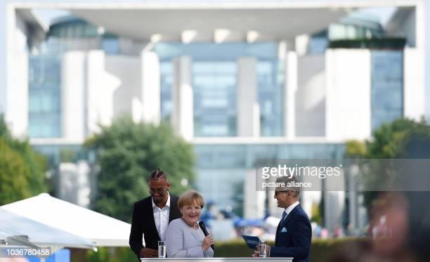 Bundeskanzlerin Angela Merkel steht am in Berlin während des Tages der offenen Tür der Bundesregierung mit Fußball-Nationalspieler Jerome Boateng auf...