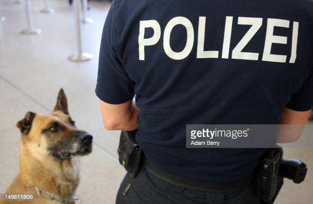 Bundespolizei police officer stands next to her K9 unit dog named Cooper at Tegel airport on August 1 2012 in Berlin Germany The topic of today's...