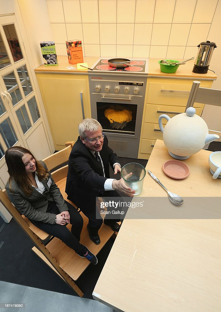 Bundestag member and Social Democrat (SPD) Fritz Rudolf Koerper and young visitor Michaela Stein explore a larger-than-life kitchen in the 'How Children See The World' exhibit in Paul-Loebe-Haus at the Bundestag on Girls' Day on April 25, 2013 in Berlin, Germany. The exhibit, which features an over-scaled kitchen complete with a breakfast table, chairs, a kitchen counter, oven and frying pan, marks the 25th anniversary of the Bundestag's Children's Commission and highlights the challenges and the dangers children face in everyday life. Girls' Day is an annual event in Germany in which adults bring teenaged girls to their workplace in order to expose them to career possibilities for later in life.