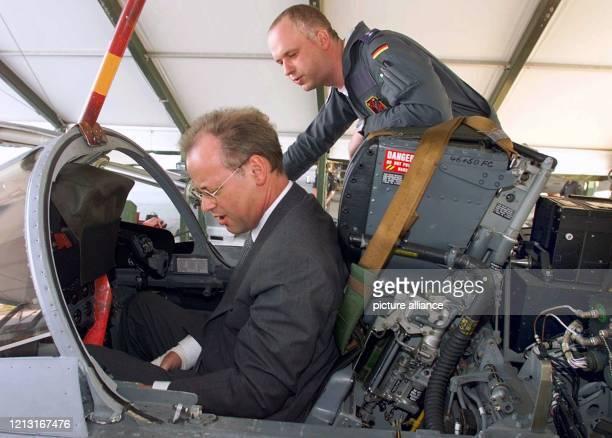 Bundesverteidigungsminister Rudolf Scharping läßt sich am 25.6.1999 im italienischen Piacenza von einem Piloten in das Cockpit eines ECR-Tornados...