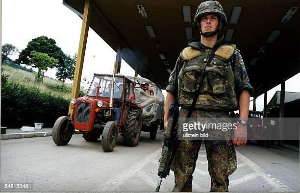 Bundeswehr - Soldat der KFOR - Truppe zur Sicherung des Grenzübergangs an der albanischen Grenze; hinter ihm die Trecks der zurückkehrenden...
