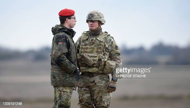 A Bundeswehr soldier and an US soldier talk together during an artillery live fire event by the US Army Europe's 41st Field Artillery Brigade at the...
