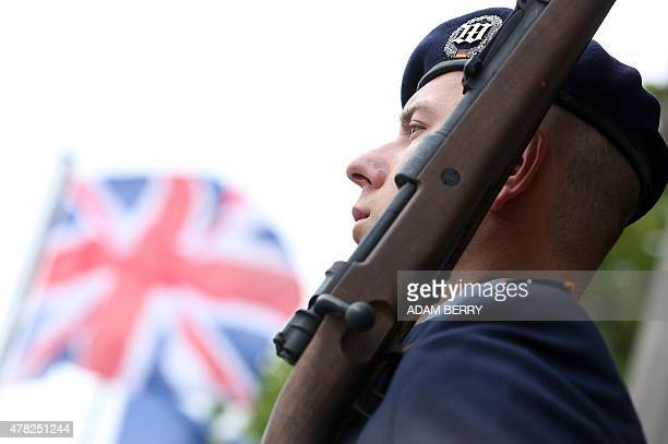 A Bundeswehr soldier stands guard as the Union Jack flutters in the background before Queen Elizabeth II arrives to lay a wreath at the memorial for...