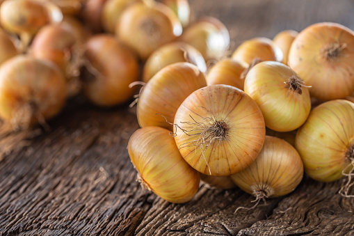 bundle of freely lying dried onion on a wooden table 1171700981