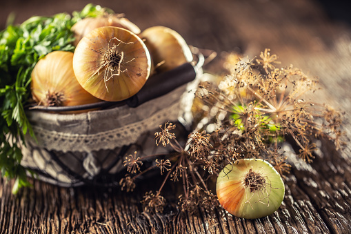 Bundle of freely lying dried onion with parsley herbs and dill in basket on a wooden table 1171701044