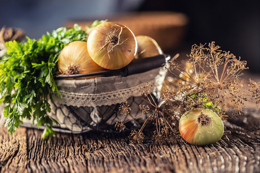 Bundle of freely lying dried onion with parsley herbs and dill in basket on a wooden table 1171701072