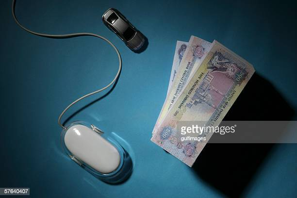 Bundle of Money with Computer Mouse and Car