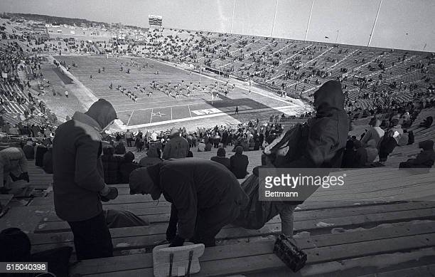 Bundled fans brush snow off seats at Lambeau Field here 12/31 as the Packers warm up for their NFL championship game with the Dallas Cowboys The...