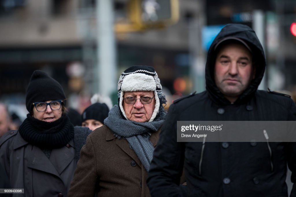 Bundled up pedestrians walk through Midtown Manhattan in below freezing temperatures, January 3, 2018 in New York City. New York City was placed under a winter storm watch Wednesday as a major weather system is expected to threaten the area with heavy snow and powerful wind Wednesday night into Thursday.