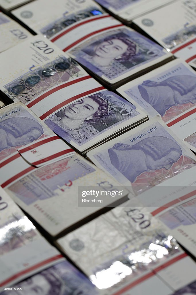 Bundles of 20 pound sterling banknotes are arranged for a photograph inside a Travelex store, operated by Travelex Holdings Ltd., in London, U.K., on Friday, Sept. 12, 2014. The pound, already suffering its worst month in more than a year, has the potential to tumble 10 percent should the Scots vote for independence from the U.K., according to economists surveyed by Bloomberg. Photographer: Matthew Lloyd/Bloomberg via Getty Images