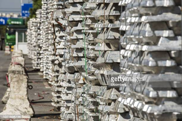 Bundles of aluminum ingots sit stacked on the side of a road near a China National Materials Storage and Transportation Corp stockyard in Wuxi China...