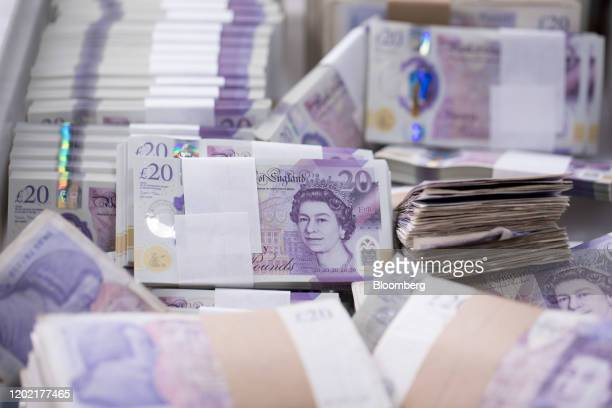 Bundles of both old cotton British 20-pound banknotes and new polymer British 20-pound banknotes sit in a basket in a warehouse operated by G4S Plc...
