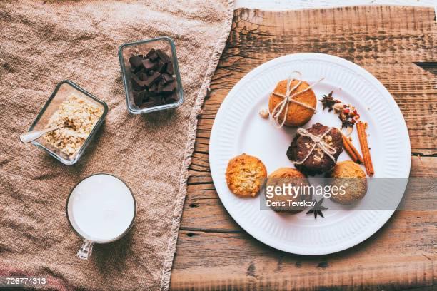 Bundles of cookies tied with string on plate near ingredients