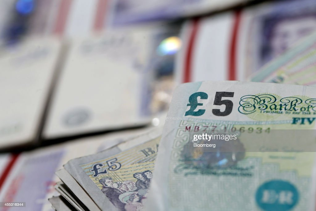 Bundles of five and 20 pound sterling banknotes are arranged for a photograph inside a Travelex store, operated by Travelex Holdings Ltd., in London, U.K., on Friday, Sept. 12, 2014. The pound, already suffering its worst month in more than a year, has the potential to tumble 10 percent should the Scots vote for independence from the U.K., according to economists surveyed by Bloomberg. Photographer: Matthew Lloyd/Bloomberg via Getty Images