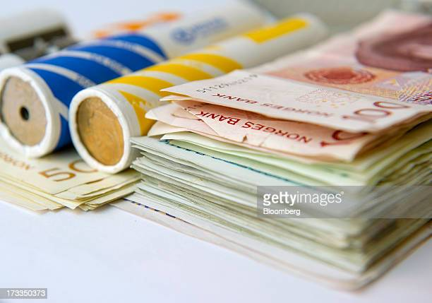 Bundles of mixed denomination Norwegian krone currency notes and coins sit in this arranged photograph in Oslo Norway on Friday July 13 2013 Norway's...