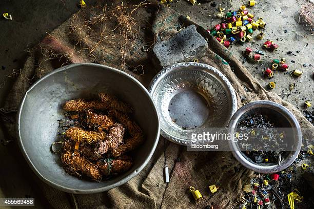 Bundles of recycled copper wire sit in a bowl as other electronic waste sits strewn across the ground at a family compound of houses in Sangrampur...